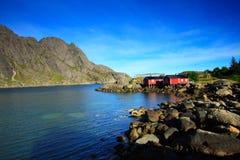 Felsen, Himmel, Meer und rote Häuser stockfotos