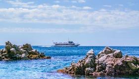 Felsen im Meer gegen das Schiff schwammen Lizenzfreie Stockfotos