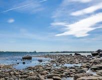 Felsen im Wasser durch das Ufer Lizenzfreie Stockfotografie