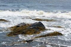 Felsen im Wasser und Wellen mit Gischt auf Strand stützen unter Lizenzfreies Stockbild