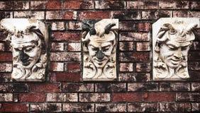 Felsen-Köpfe, die aus Backsteinmauer herauskommen Lizenzfreies Stockfoto