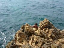 Felsen, Meer und junger Mann Stockbild
