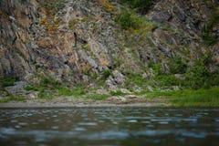 Felsen mit orange Flechte, szenische Ansicht vom Fluss Stockbilder