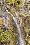 Felsen mit Wasserfall im Herbstberg Stockfoto