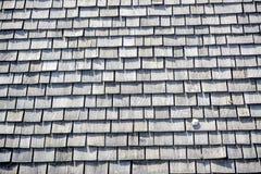 Felsen sitzt auf einem Holz geschichteten Dach lizenzfreie stockfotografie