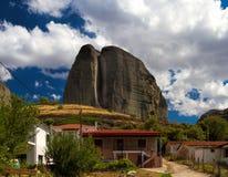 Felsen steigt über die Häuser in Meteora Lizenzfreie Stockbilder