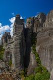 Felsen steigt über die Häuser in Meteora Lizenzfreie Stockfotos