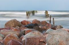Felsen und Überreste einer Anlegestelle an der Küste Stockfoto