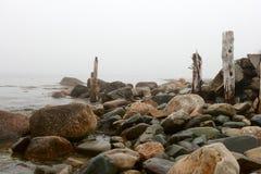 Felsen und alte hölzerne Beiträge an der Bucht Lizenzfreies Stockfoto