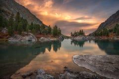 Felsen und Bäume, die im rosa Wasser von Sonnenuntergang-Mountainsee, Altai-Gebirgshochland-Natur Autumn Landscape sich reflektie stockfotos