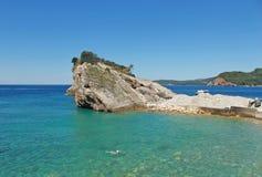 Felsen und Boot auf Insel von Sankt Nikolaus in Budva, Montenegro Paradiesstrand auf Insel im Meer Konzept der Reise lizenzfreie abbildung