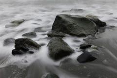 Felsen und glattes Wasser Stockbild