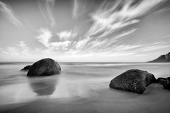 Felsen und Ozean unter einem bewölkten Himmel im Monochrom stockbild