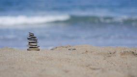 Felsen und Sand auf einem Hintergrund von Ozean Stockbilder