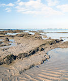 Felsen und Sand setzen vertikal auf den Strand Stockbild