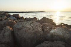 Felsen und Steine auf dem Strand mit Pier bei Sonnenaufgang Stockfotografie