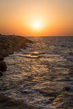 Felsen und Wellen bei Sonnenuntergang Stockfotografie