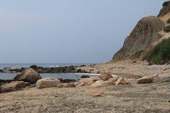 Felsen unter den Klippen auf Strand Lizenzfreie Stockfotos