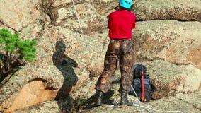 Felsenbergsteiger, der einer Klippe anhaftet stock footage