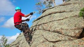 Felsenbergsteiger, der einer Klippe anhaftet stock video