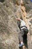 Felsenbergsteiger, der einer Klippe anhaftet Stockfotografie