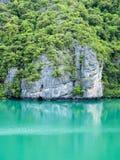 Felsenhügelreflexion auf grünem Meerwasser lizenzfreie stockfotografie