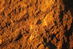 Felsenhintergrund in der gelben Leuchte Stockfotografie