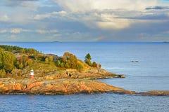 Felseninsel mit Leuchtturm von Helsinki-Archipel bei Sonnenuntergang Entfernter Regenbogen im Meer lizenzfreies stockbild