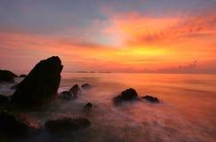 Felsenstrandschattenbild am Sonnenaufgang Stockbild