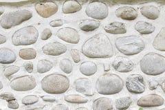 Felsenwand von natürlichen Flusssteinen Runder Steinwandhintergrund Fluss-rundes Steinmuster Kleine rote Steine Fluss schaukelt b Stockbild