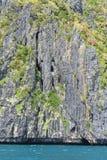 Felsformation mit den Anlagen befestigt zu ihr über einem blaugrünen Meer stockbilder