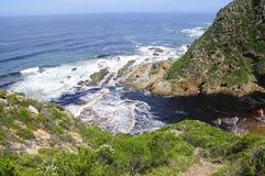Felshügel durch den Ozean Stockbild