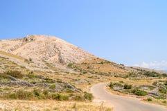 Felshügel und Zäune mit der Straße auf der Insel von Krk, kroatisch Stockbild