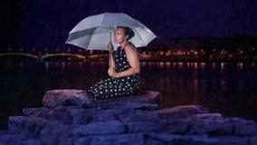 Felsig, weibliches Modell Regenkniens Stockfotos