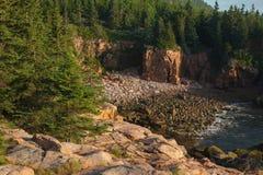 Felsige abgelegene Buchteinfassung durch hohe rosa Granit-Felsgelände Lizenzfreie Stockfotos