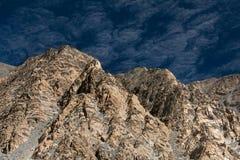 Felsige Felsen der rosa Farbe mit weißen Adern des Quarzes auf Hintergrund des dunklen blauen Himmels des Indigos mit Wolken, abs Lizenzfreies Stockbild