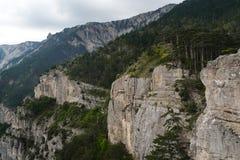 Felsige Gebirgsklippe und blauer Himmel mit weißen Wolken Stockfotos