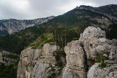 Felsige Gebirgsklippe und blauer Himmel mit weißen Wolken Stockbild
