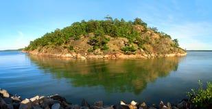 Felsige Insel im blauen Meer Lizenzfreies Stockfoto