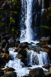 Felsige isländische Landschaft mit einem Wasserfall Stockfotos