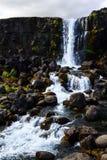 Felsige isländische Landschaft mit einem Wasserfall Stockfotografie