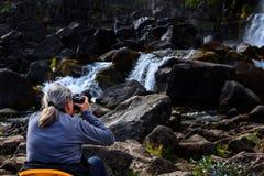 Felsige isländische Landschaft mit einem Wasserfall Lizenzfreie Stockfotos