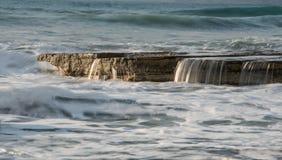 Felsige Küste mit gewelltem Ozean und Wellen, die auf den Felsen zusammenstoßen stockbild