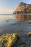 Felsige Küste in den Strahlen des aufgehende Sonne Lizenzfreies Stockfoto