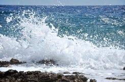 Felsige Küste mit dem Spritzen von Wellen Stockfotografie