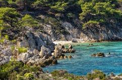 Felsige Küste mit einem kleinen versteckten sandigen Strand, in Chalkidiki, Griechenland Lizenzfreies Stockbild