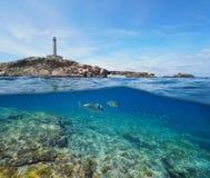 Felsige Küste mit einem Leuchtturm und Unterwasser-, aufgeteilte Ansichthälfte über und unter Wasseroberfläche fischen lizenzfreie stockbilder