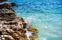 Felsige Küste mit Spritzenwasser vor blauem Meer Stockfoto