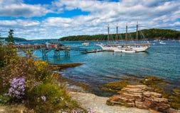 Felsige Küste und Ansicht von Booten im Hafen an der Stange beherbergten, Maine Lizenzfreie Stockbilder