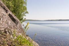 Felsige Küste von hölzernem See Stockfotografie